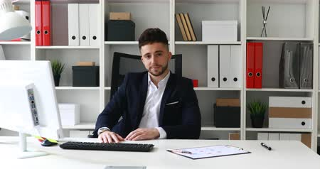 vazo : young businessman making gesture with hand and looking at camera