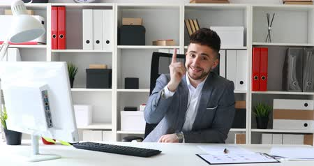 approving : young businessman sitting at table in white office, smiling and showing approving hand gesture.