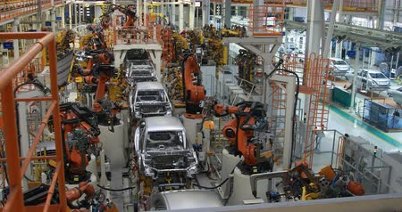 soudure : Assembly line production of new car. Automated welding of car body on production line. robotic arm on car production line is working Vidéos Libres De Droits