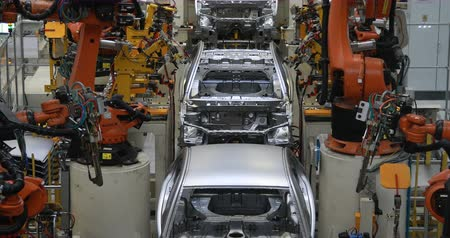 дружелюбный : Assembly line production of new car. Automated welding of car body on production line. robotic arm on car production line is working Стоковые видеозаписи