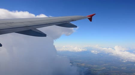 Aircraft decreases altitude among the clouds. The view from an airplane window.