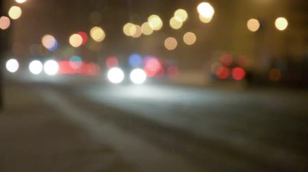 Night street with bokeh lights in the snowstorm.