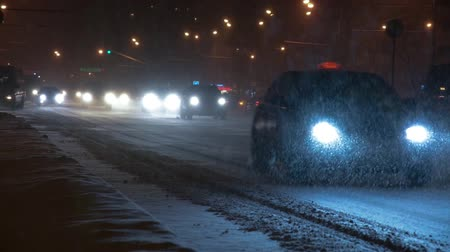 Cars on the city road in a snowstorm at night.