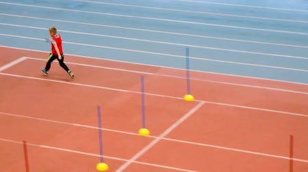 Boy running in the relay at the athletics training in sport school