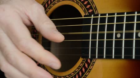 closeup footage of a man playing an acoustic guitar