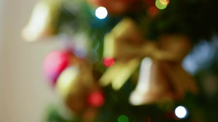 Rack focus Christmas ornaments and electric lights on tree