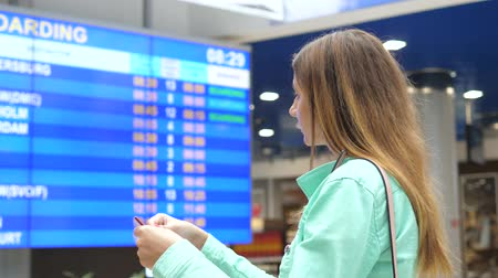 jóquei : Young Woman Looks At The Information Board Of Departures At The Airport.