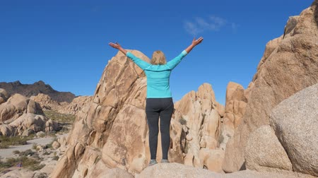 climbed : Portrait Woman Standing On The Edge Of A Cliff Raised Hands Up And To The Side