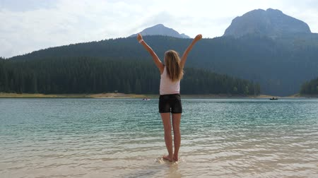 olhares : Woman Standing On Rock In Mountain Lake Stretched His Hands Up To The Sides Vídeos