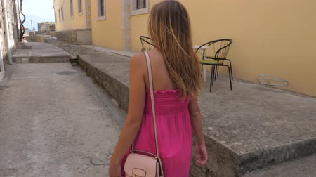 persiana : Young Woman In Pink Dress Walk On The Old Stone Town Street, View From The Back