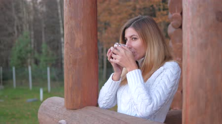 günlüğü : Woman In White Sweater With Cup Of Tea Is Goes On The Veranda Of A Wooden House