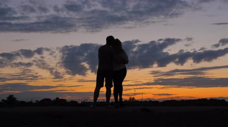 večer : Silhouette romantic couple, looked at the scarlet sunset, hugging each other.