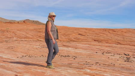 took : Tourist Hiking In Desert Woman Walking On The Park Red Rock Slow Motion 4K Stock Footage