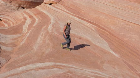 took : Tourist Woman Descends From The Top Of The Hill On The Colored Stone Red Rocks