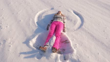 hazugság : Cheerful Young Woman On A Sunny Day In The Winter Making Snow Angels Slow Motion