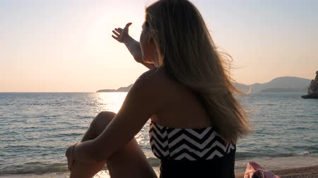 hides : Female Hands Catch The Sun In The Sky Sitting On Beach Sea