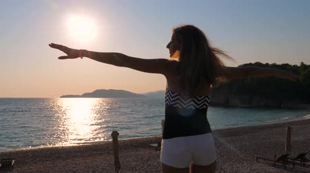 hides : Tourist Woman Enjoying the Sunset On Sea, Hands Straightens Hair And Flying