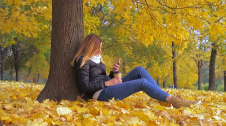 ntsc : Woman Sitting With His Back To The Tree In Yellow Autumn Leaves, Uses Smartphone Stock Footage