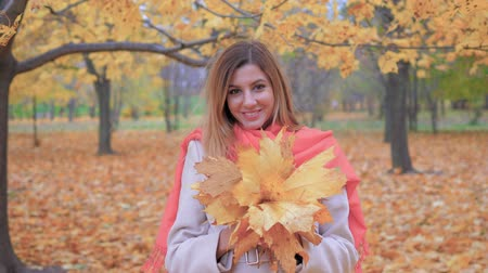 sincerely : Lady In Beige Coat And Orange Scarf Holding Bouquet Yellow Autumn Leaves Stock Footage