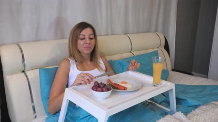 linen : Woman Eating Breakfast Sausages With Scrambled Eggs On The Table, Lying In Bed Stock Footage