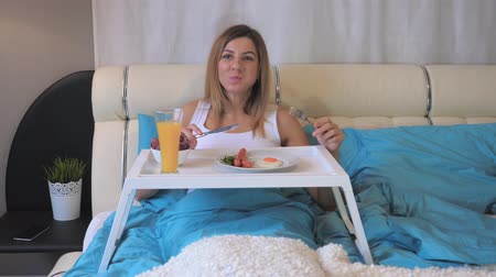 egg laying : Woman Eating Breakfast Sausages With Fried Eggs On The Table, Lying In Bed
