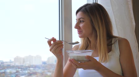 corn flakes : Woman Eating Cereal With Milk Out Of Bowl Standing At Window And Looking Outside Stock Footage