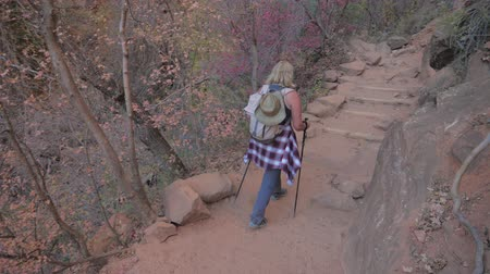 íngreme : Active Woman Hiking Down A Steep Trail Over Huge Rocks In Mountains Zion Park