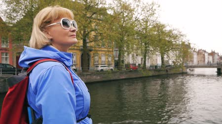 bruges : Woman Tourist Stands At River Canal, On Which Float Tour Boat In Old Stone Town Stock Footage