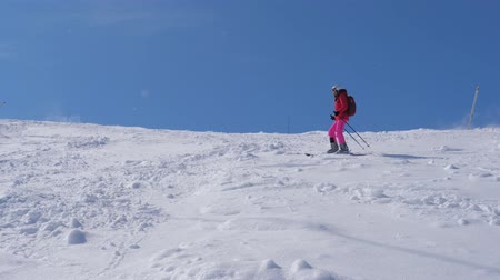 hegyoldalban : Woman Slowly Rolls Down The Mountain Skiing On A Steep Slope With Boulders Stock mozgókép