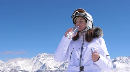 tampado : Woman Skier Drinking Clean Water From A Plastic Bottle On A Mountain Background