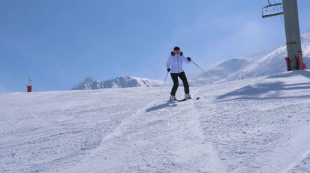 sporty zimowe : In Movement Woman Skier Carving Go Down The Ski Slope Of Mountain Near Chairlift