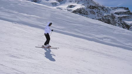 blood sport : In Movement Side View, Woman Skier Skiing Down The Slope Of The Mountain On Skis