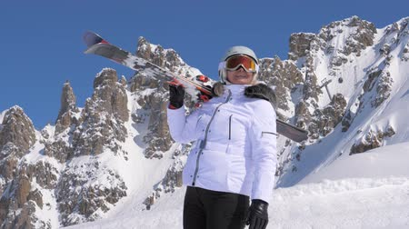 admires : Woman skier with skis on her shoulder admires beauty of nature in the mountains Stock Footage