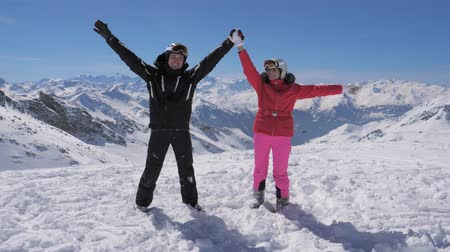 keşif : Happy skiers couple stands on the mountain peak and rises their hands Stok Video