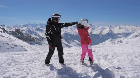 keşif : Skiers saw something interesting in the mountain valley and hand show each other