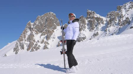 admires : Woman Skier Stands On The Side Of A Mountain Holding Skis