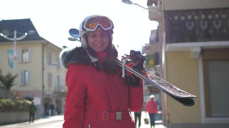 admires : Attractive Woman Stands Near Houses Holding Her Downhill Ski Before Skiing