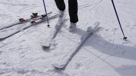 ski boots : A Skier Puts On His Downhill Ski On White Ski Boots Stock Footage