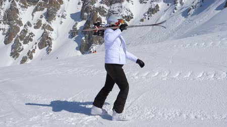 ne : A Skier Go Forward With Downhill Ski On Ner Shoulder