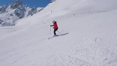 blood sport : Sporty Woman Skis Carving Down The Slope In The Mountains Ski Resort At Winter