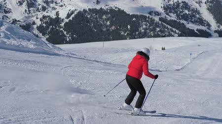 blood sport : Mature Woman Skier Carving Down The Slope In The Mountains Ski Resort At Winter