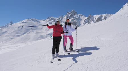 admires : Skiers Saw Something Interesting In The Mountain Valley And Show Each Other Stock Footage