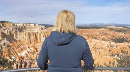 admires : A Tourist Mature Woman Looks The Natural Beauty Of The Bryce Canyon