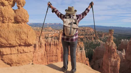 pólos : A Hiker Woman Raises Her Hands, Standing Over The Edge Of The Bryce Canyon