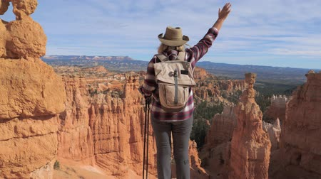 enjoys : A Hiker Woman Raises Her Hand, Standing Over The Edge Of The Bryce Canyon