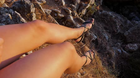дубленый : Close Up Of Female Legs Swaying At The Rocky Cliff
