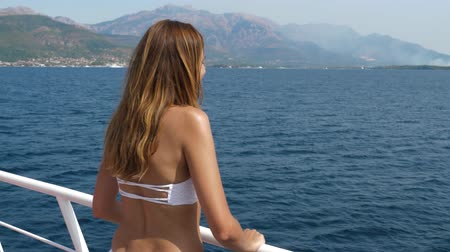 standlar : Tanned Young Woman Stands On Board The Ship And Observes The Sea Stok Video