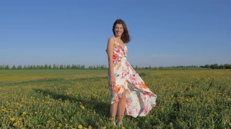 pampeliška : Portrait Of A Smiling Woman Standing In A Blooming Yellow Field In A Dress