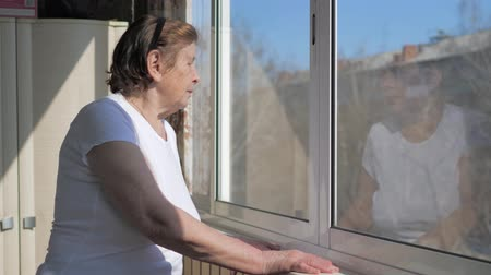 трепет : An Old Woman Stands By The Window And Looks Outside In Sunny Weather