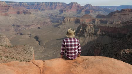 planalto : Man Sitting Alone On Edge Of The Abyss Looking Amazing View Of Grand Canyon Stock Footage